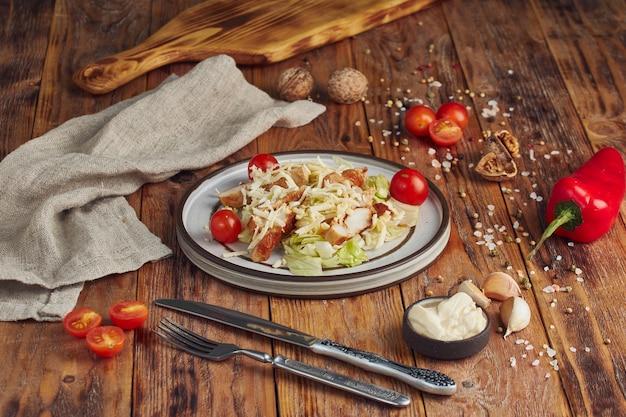Caesar salade met kip in een witte plaat op houten tafel Premium Foto