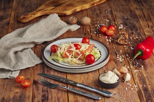 Caesar salade met zalm in witte plaat op houten tafel. lekkere zeevruchtensalade. Premium Foto
