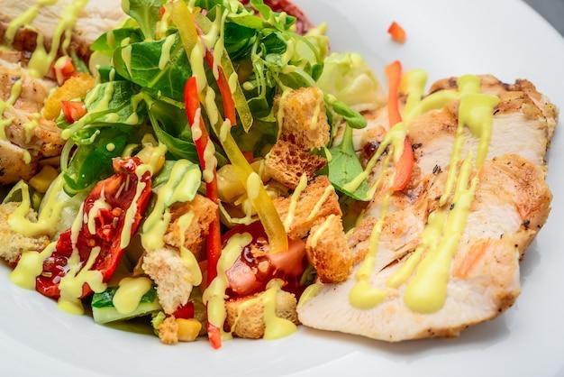 Caesarsalade met croutons, kwartelseieren, cherrytomaten en gegrilde kip op een houten tafel Premium Foto