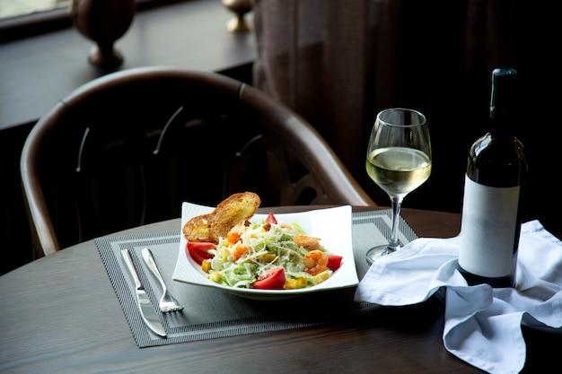Caesarsalade met garnalen en glas witte wijn Gratis Foto
