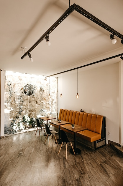 Café interieur met een oranje bank, drie tafels en drie zwarte stoelen Gratis Foto