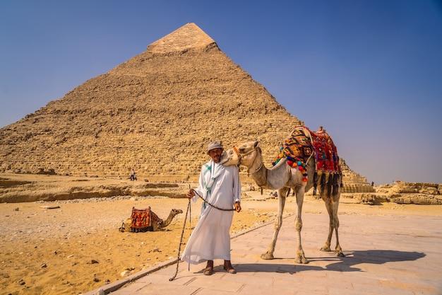Caïro, egypte; oktober 2020: een lokale verkoper met zijn kameel bij de piramide van kefren. de piramides van gizeh, het oudste grafmonument ter wereld Premium Foto