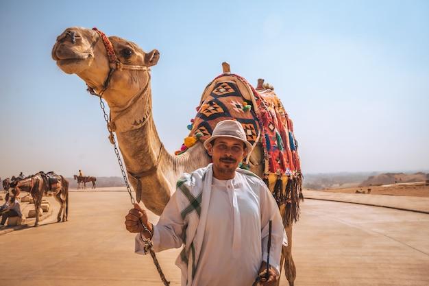 Caïro, egypte; oktober 2020: portret van een lokale verkoper met zijn kameel bij de kefren-piramide. de piramides van gizeh, het oudste grafmonument ter wereld Premium Foto