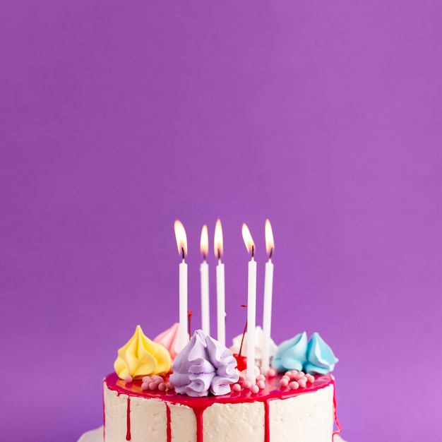Cake met aangestoken kaarsen op purpere achtergrond Gratis Foto