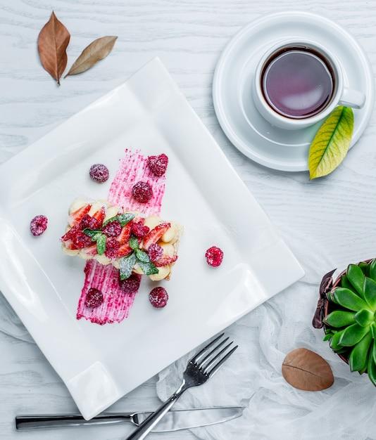 Cake met aardbeien en thee op de tafel Gratis Foto