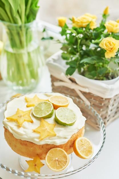 Cake met citroenen, limoenen, carambola op de tafel naast de tulpen Premium Foto
