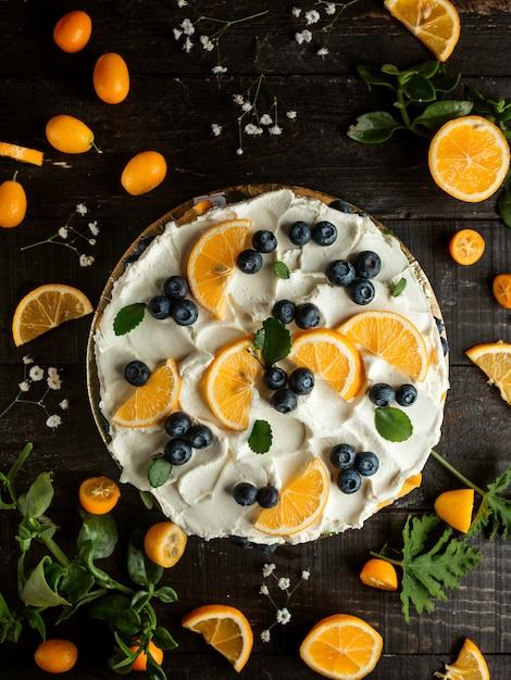Cake met crème bosbessen citroen kumquat en bloemen op tafel Gratis Foto