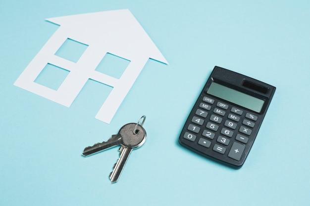 Calculator en sleutels met document knipsel van huis over achtergrond Gratis Foto
