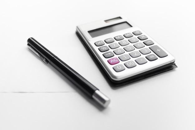 Calculator met een pen en document nota met geïsoleerd schuldwoord Premium Foto