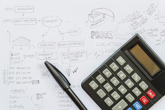 Calculator met pen op businessplan papier Gratis Foto