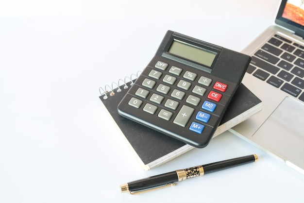 Calculator op laptop met pen in de buurt van de laptop Premium Foto