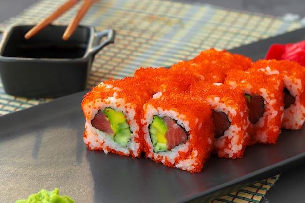 California sushi roll geserveerd op zwarte keramische plaat close-up Premium Foto