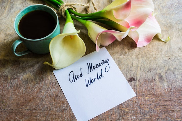 Calla bloemen en kop og koffie op rustieke lijst Premium Foto