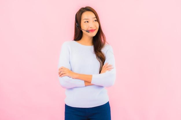 Callcenter van de portret het mooie jonge aziatische vrouw op roze kleur geïsoleerde muur Gratis Foto