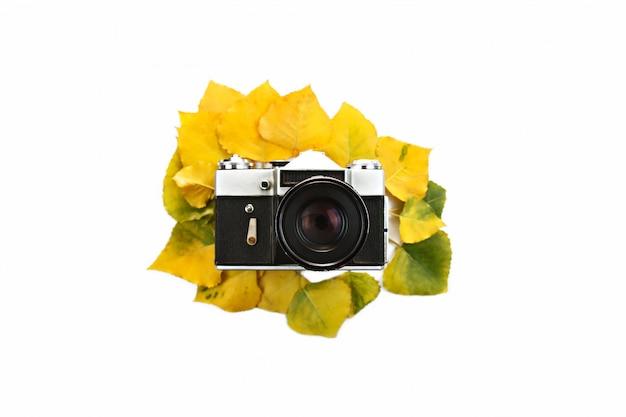 Camera met lens op kleurrijke herfstbladeren in het midden. bespotten. geïsoleerd op wit Premium Foto