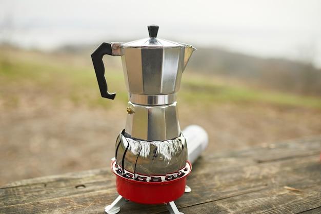 Campingkoffie buiten met metalen geiser koffiezetapparaat op een gasbrander, stap voor stap. Premium Foto