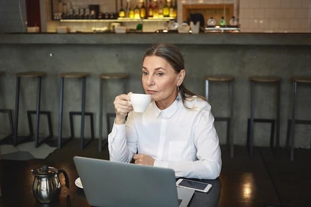 Candid shot van doordachte rijpe zakenvrouw in formeel shirt genieten van koffie tijdens de lunch, zittend in café met generieke laptop en leeg scherm mobiele telefoon op tafel. bedrijf, leeftijd en technologie Gratis Foto