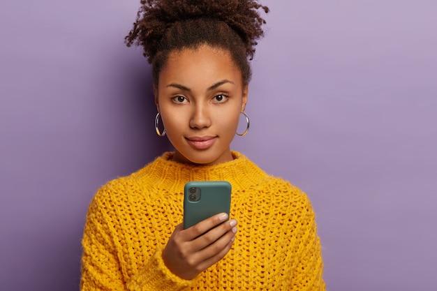 Candid shot van ernstige duizendjarige vrouw met donker krullend haar, mobiele telefoon gebruikt, kijkt direct naar de camera, draagt gele kleding Gratis Foto