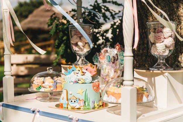 Candy bar voor je verjaardag. kinderfeestje in pastelkleuren in de natuur. mooie zoete cake, hand marshmallows, cupcakes, lollies, meringues. Premium Foto