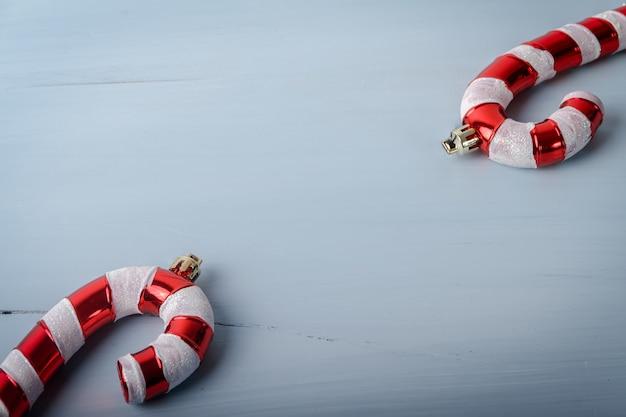 Candy cane vormige kerst speelgoed op een witte gebarsten houten oppervlak met een kopie ruimte Gratis Foto