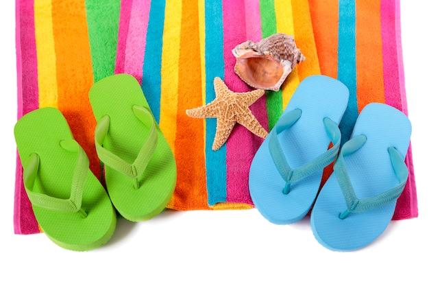 Candy stripe strandlaken met flip flops, zeester en zeeschelp op wit wordt geïsoleerd. Gratis Foto