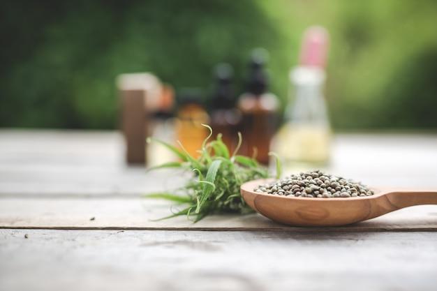 Cannabis, cannabis zaden, cannabis olie geplaatst op een houten vloer met een groene boom op de achtergrond. Gratis Foto
