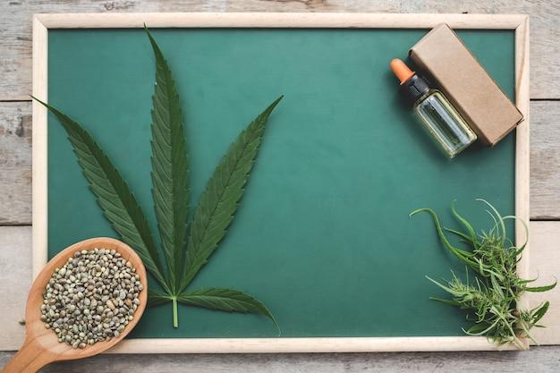 Cannabis, cannabiszaden, cannabisbladeren, cannabisolie geplaatst op een groen bord op een houten vloer. Gratis Foto