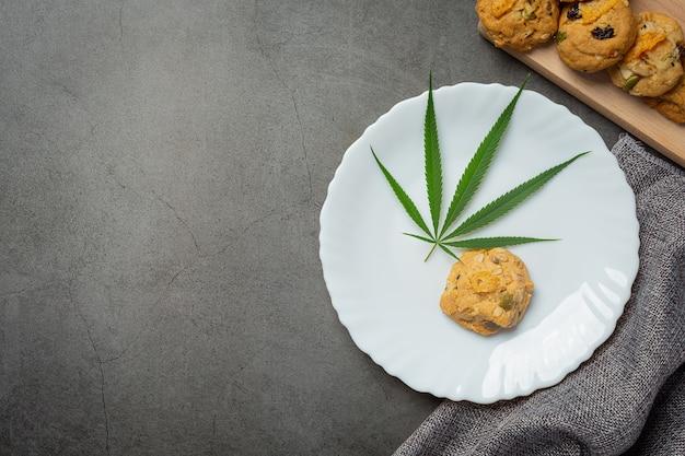 Cannabis koekje en cannabisblad op een witte plaat Gratis Foto