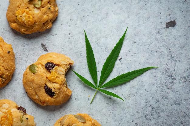 Cannabiskoekjes en cannabisbladeren op de vloer Gratis Foto