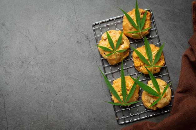 Cannabiskoekjes en cannabisbladeren op een donkere vloer Gratis Foto