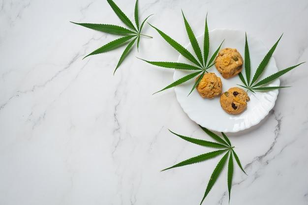 Cannabiskoekjes en cannabisbladeren op een witte plaat Gratis Foto