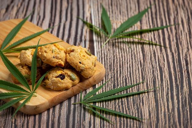 Cannabiskoekjes en cannabisbladeren op houten snijplank Gratis Foto