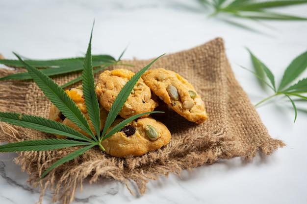 Cannabiskoekjes en cannabisbladeren op stof Gratis Foto
