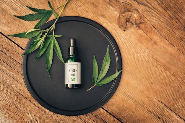 Cannabs medisch product, cbd-olie, met hennepbladeren op een zwarte schaal op een houten tafel. plat leggen. mockup kopieer spase Premium Foto