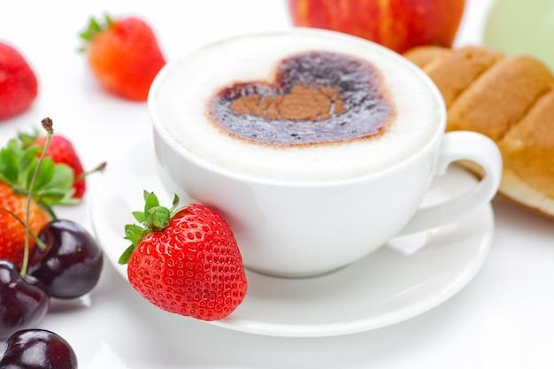 Cappuccino in een kopje in de vorm van harten, kers, croissant en Premium Foto
