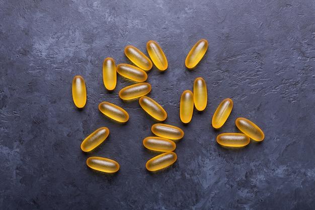 Capsules omega 3 op donkere stenen achtergrond close-up gezondheidszorg concept Premium Foto