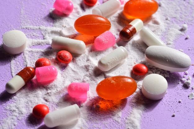 Capsulespillen gebroken met uw poedermedicijn op violette achtergrond Premium Foto