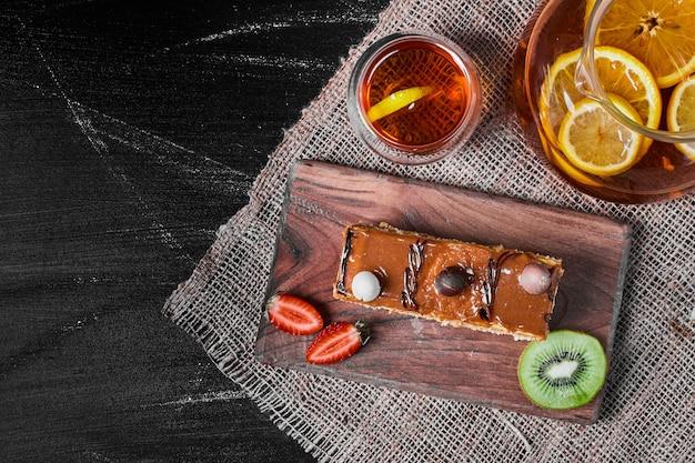 Caramel cake slice op een houten schotel. Gratis Foto