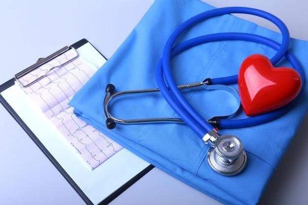 Cardiogram met medische stethoscoop en rood hart met artsenlaag op lijst Premium Foto