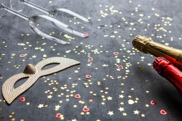 Carnaval-maskers, champagneflessen en twee champagneglazen en gouden glitter confetti, Premium Foto