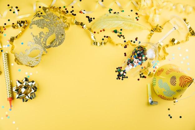 Carnaval-veermasker met het materiaal van de partijdecoratie en partijhoed op gele achtergrond Gratis Foto