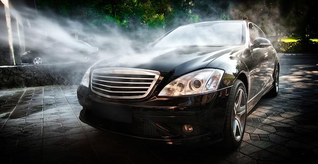 Carwash. een auto schoonmaken met water onder hoge druk. Premium Foto