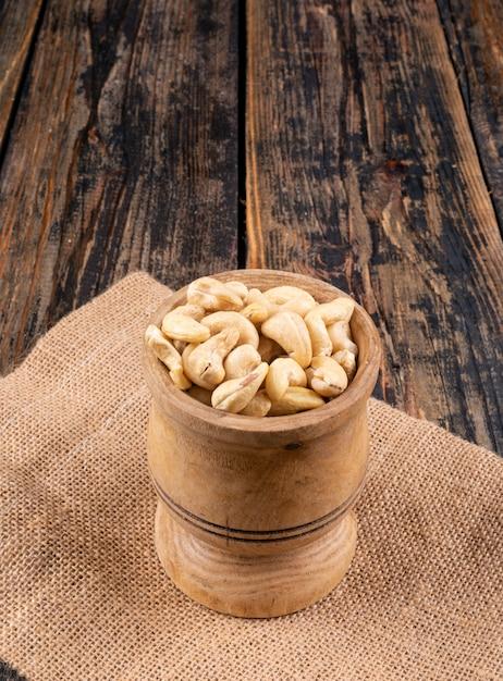 Cashew in een houten kop zijaanzicht op een stuk zak Gratis Foto
