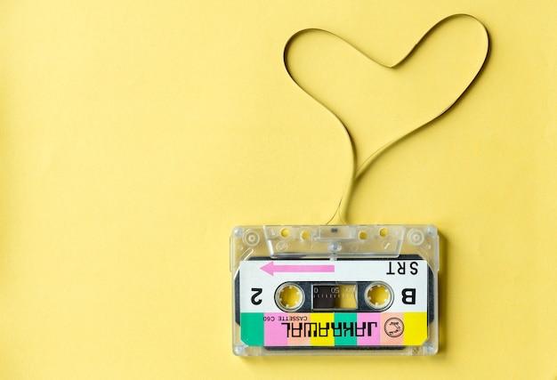 Cassetteband met een hartsymbool op gele achtergrond wordt geïsoleerd die Gratis Foto