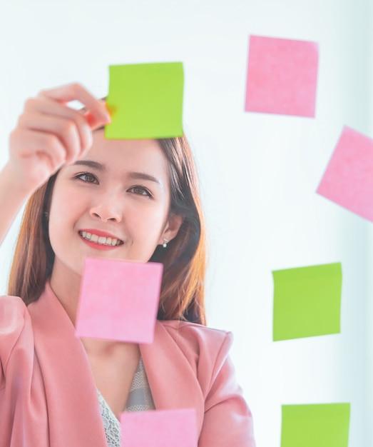Casual creatieve zakenvrouw schrijft ideaal en doel op naar de ramen Premium Foto