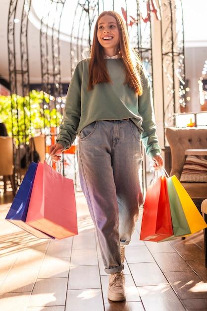 Casual geklede vrouw met boodschappentassen Gratis Foto