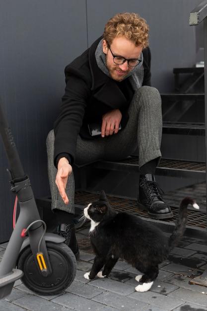 Casual mannetje dat een kat aait Gratis Foto