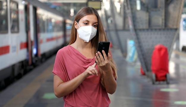 Casual vrouw met behulp van slimme telefoon in treinstation Premium Foto