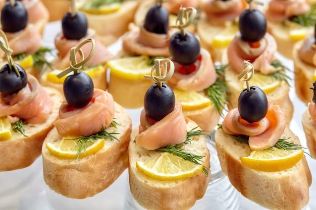 Catering van canapé met olijven, citroen en zalm Premium Foto