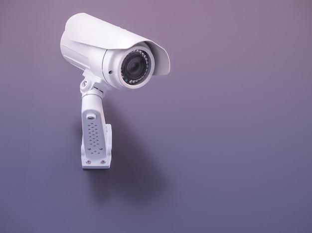 Cctv-camerabeveiliging op de paarse muur Premium Foto